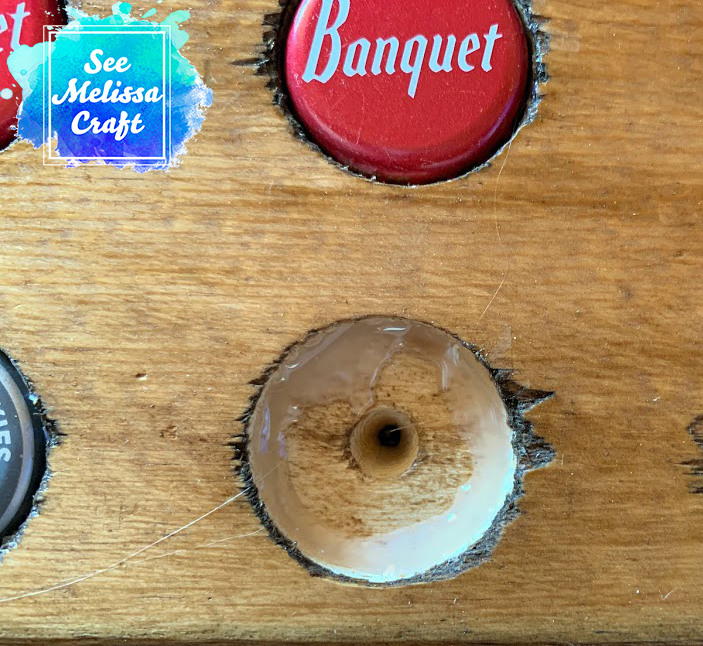 Add a circle of hot glue around the edge of your bottle cap hole